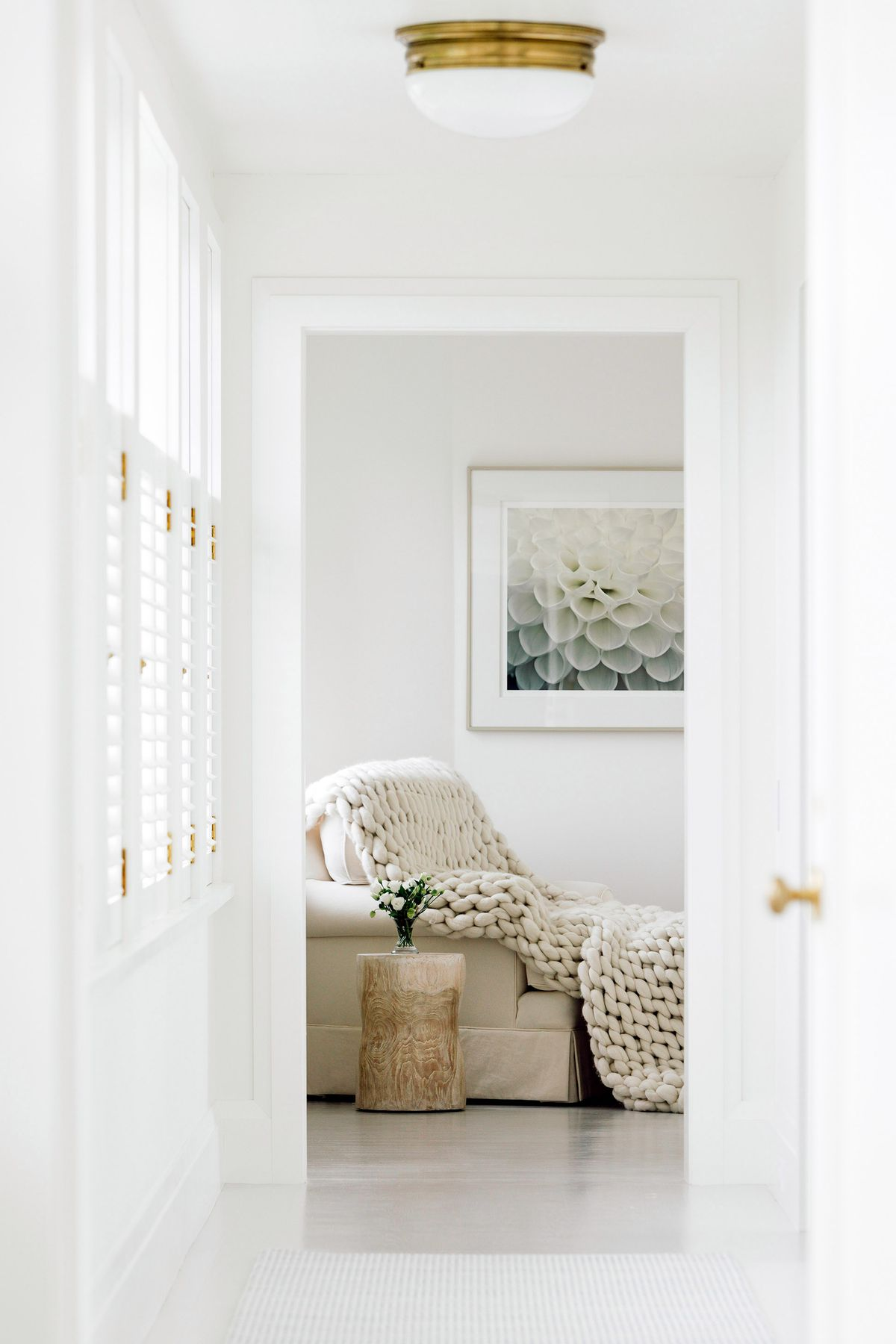 A room at the end of a long white hallway with a white sofa, chunky white blanket, and natural wood stump occasional table.