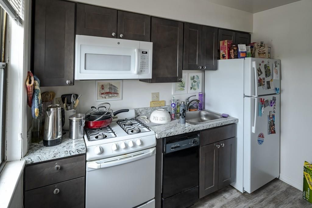A kitchen with a run of counters and cabinetry next to the fridge.