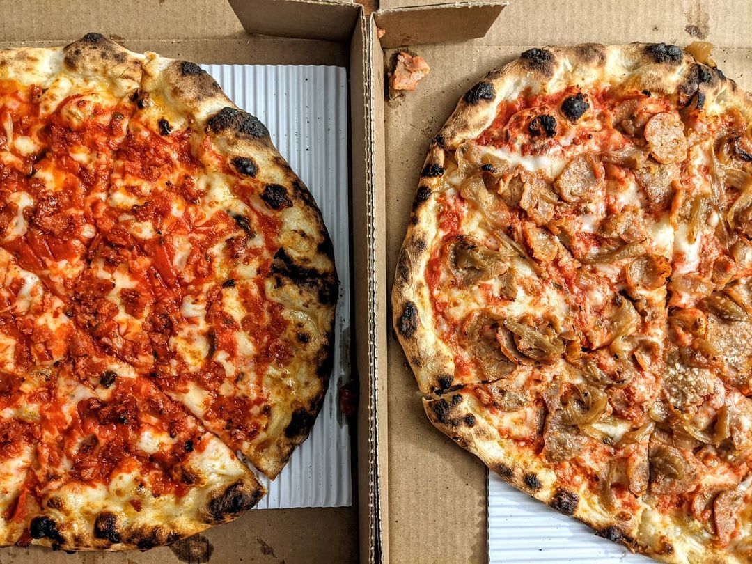 Overhead view of two pizzas side by side in cardboard boxes. The crusts are dotted with char.
