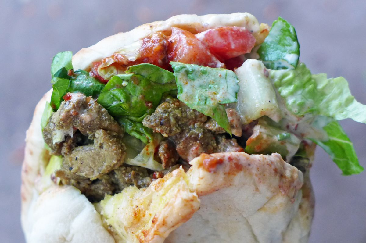 Lamb shawarma sandwich in a pita with greenery held by a hand.