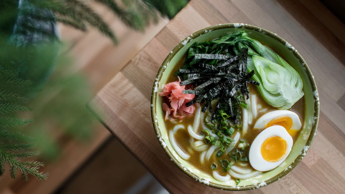A bowl of udon noodles with boiled eggs, green nori, baby bok choy, and pink pickled radishes at Ima in Corktown.