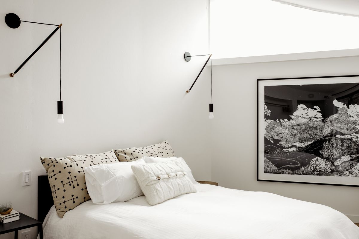 A bedroom. The bed has white bed linens with multiple assorted pillows. There is a large black and white work of art hanging on the wall. There are two light fixtures hanging above the bed.
