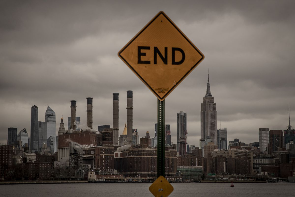 """A sign with the word """"end"""" in all capital letters stands in front of the New York City skyline"""