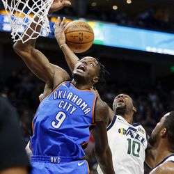 Utah Jazz guard Alec Burks pulls in a rebound behind Oklahoma City Thunder forward Jerami Grant during NBA basketball in Salt Lake City on Saturday, Dec. 23, 2017.