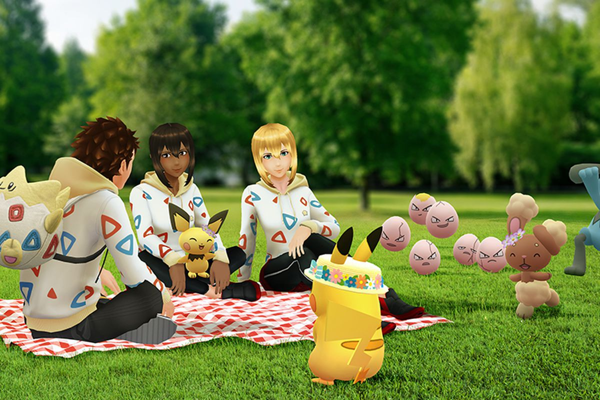 Pokémon Go trainers sit on a picnic blanket surrounded by Pokémon in flower crowns