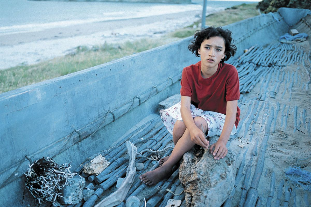 Keisha Castle-Hughes, wearing a bright red shirt, sits in a vivid blue boat in Whale Rider