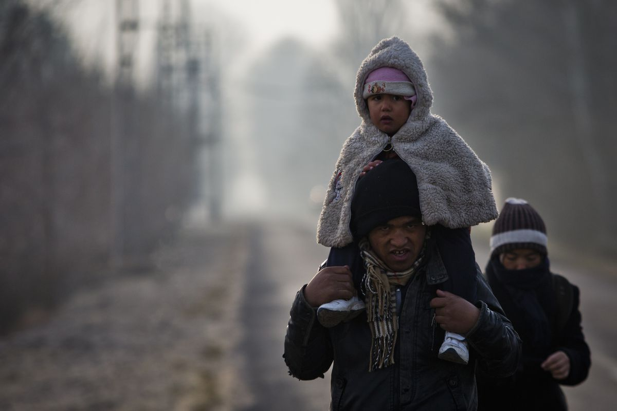 A group of Afghan migrants preparing to seek asylum at the border of an EU country.