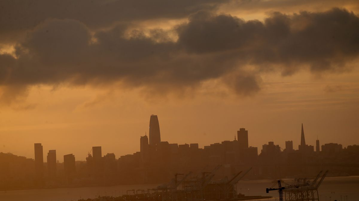 A cityscape at sunset under a series of pregnant clouds.