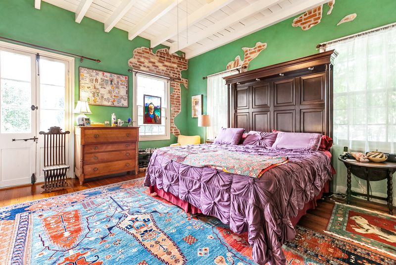 Colorful bedroom with green walls peeling to exposed brick, ceiling beams and a massive bed with wooden headboard