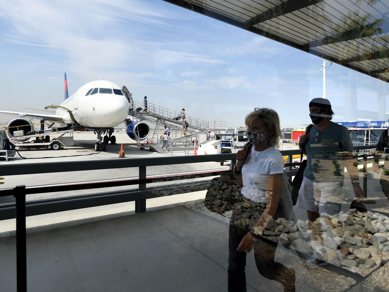 Les passagers aériens marchent sur un trottoir et un avion se trouve à l'arrière-plan.
