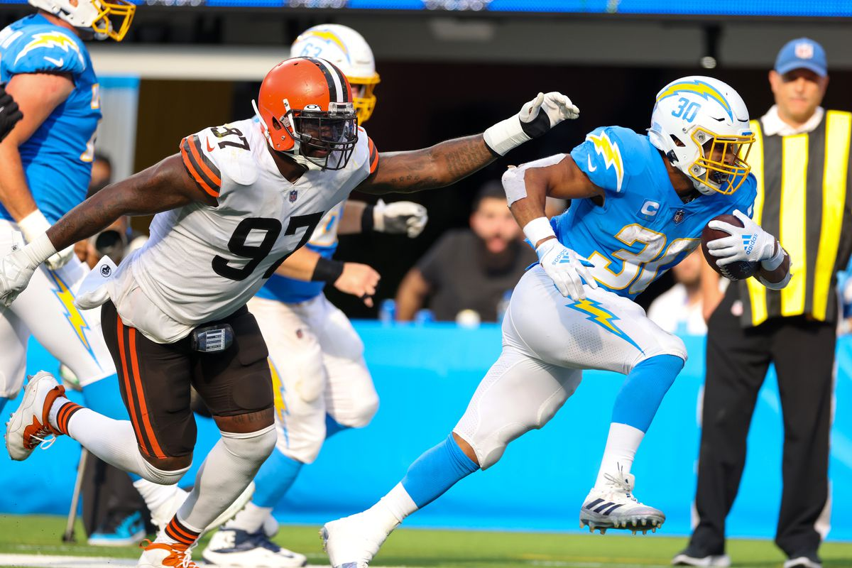 Austin Ekeler #30 of the Los Angeles Chargers runs the ball passed Malik Jackson #97 of the Cleveland Browns during the fourth quarter at SoFi Stadium on October 10, 2021 in Inglewood, California.
