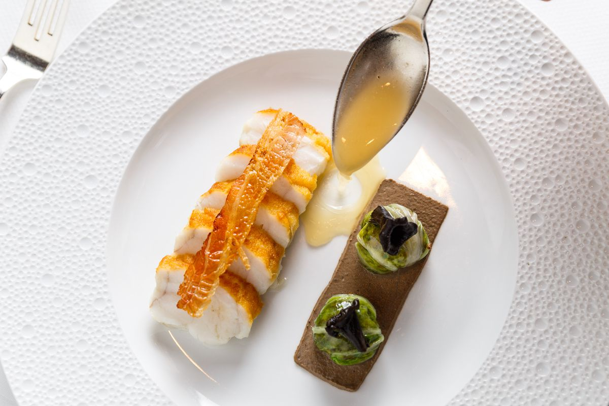 Rings of monkfish sit adjacent wild mushroom-stuffed cabbage while a waiter pours bacon jus onto the plate