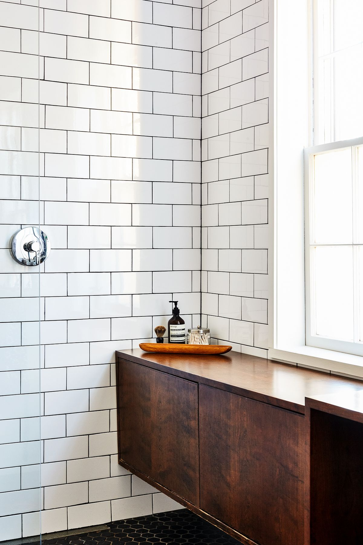 The corner of a bathroom. There are white tiles on the wall and wooden cabinetry. There is a window letting in natural light.