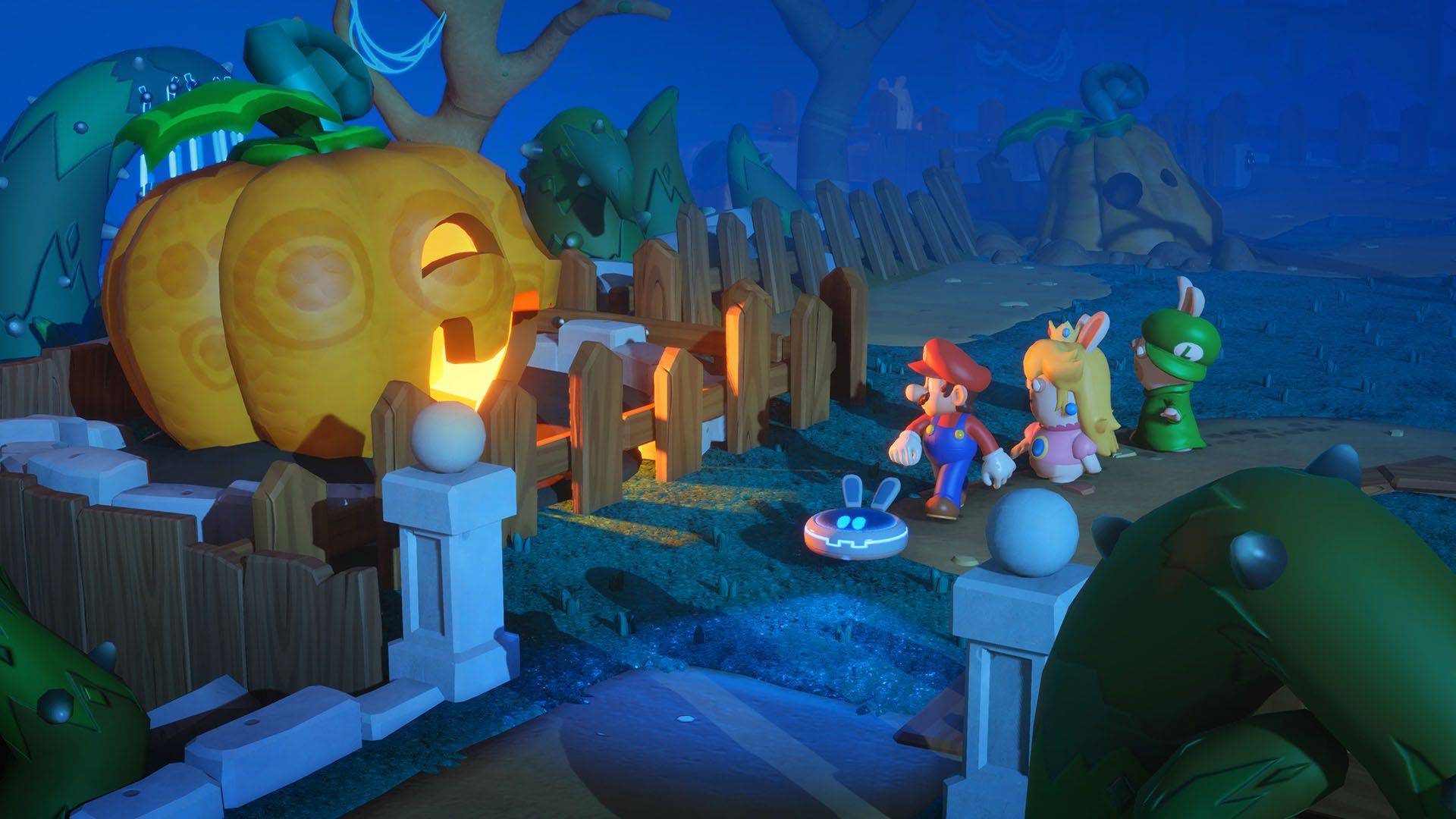 In this screenshot for Mario + Rabbids Kingdom Battle, Mario is walking in a creepy, nighttime setting, trailed by a rabbid dressed as Princess Peach and another dressed as Luigi. The team is walking past a large jack-o-lantern with a glowing mouth and ey