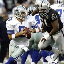 Dallas Cowboys quarterback Tony Romo (9) drops back to pass as Oakland Raiders defensive tackle Gerard Warren (61) pursues.