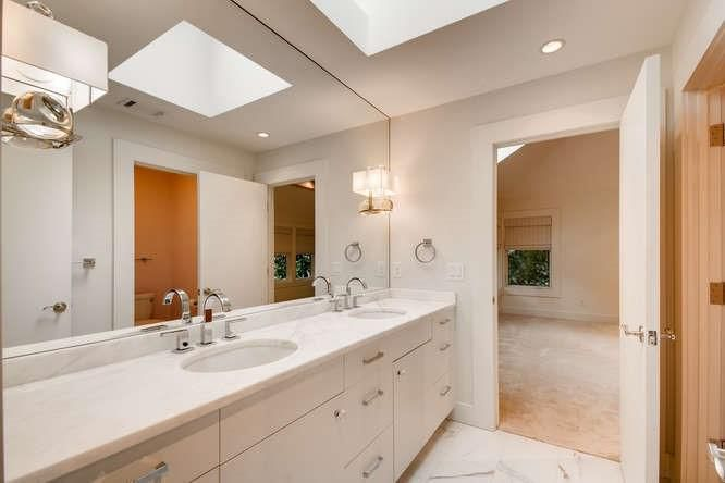A white bathroom with a long mirror and two sinks.