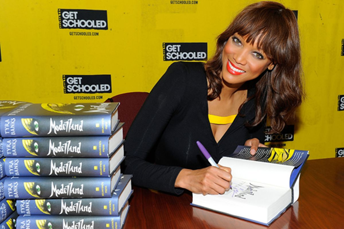 Tyra Banks signs books at an event in October. Via Getty.