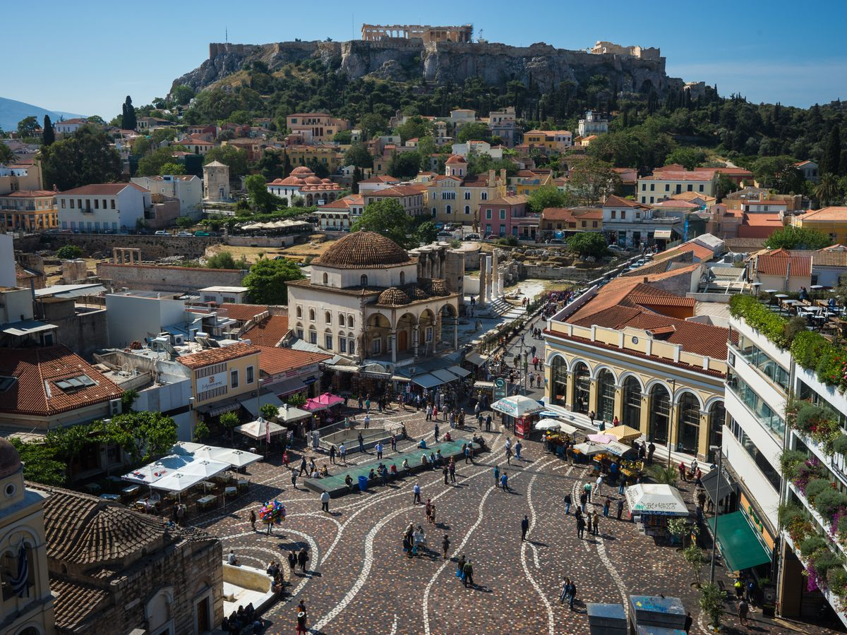 An aerial view of Monastiraki Square in Athens. There is a large courtyard surrounded by various buildings. In the distance are mountains.