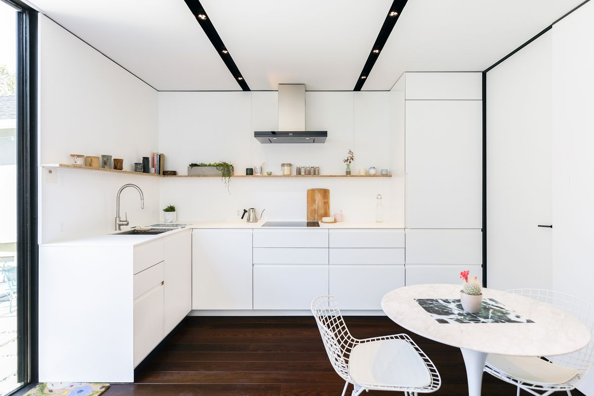 All-white dining room and kitchen.