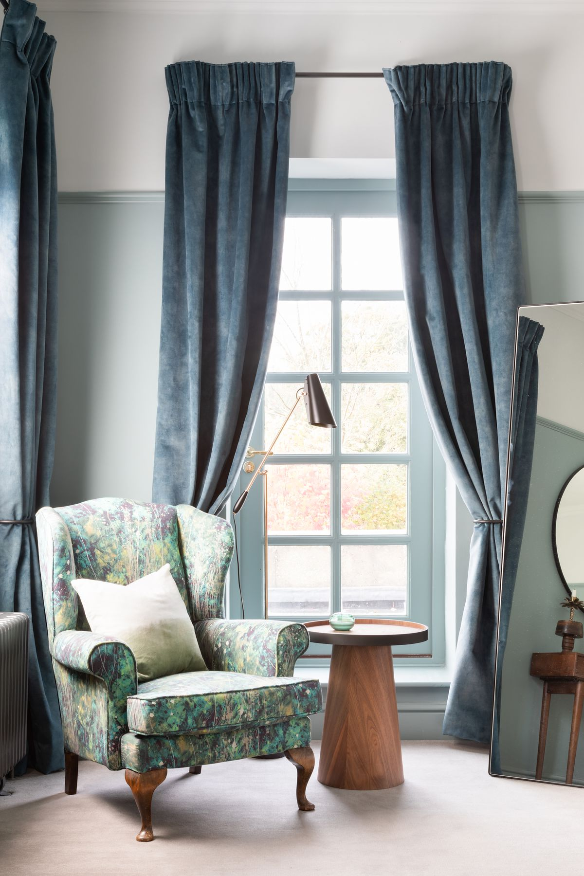 Blue gradient curtains flank a tall window. A patterned armchair and wooden side table sit nearby.