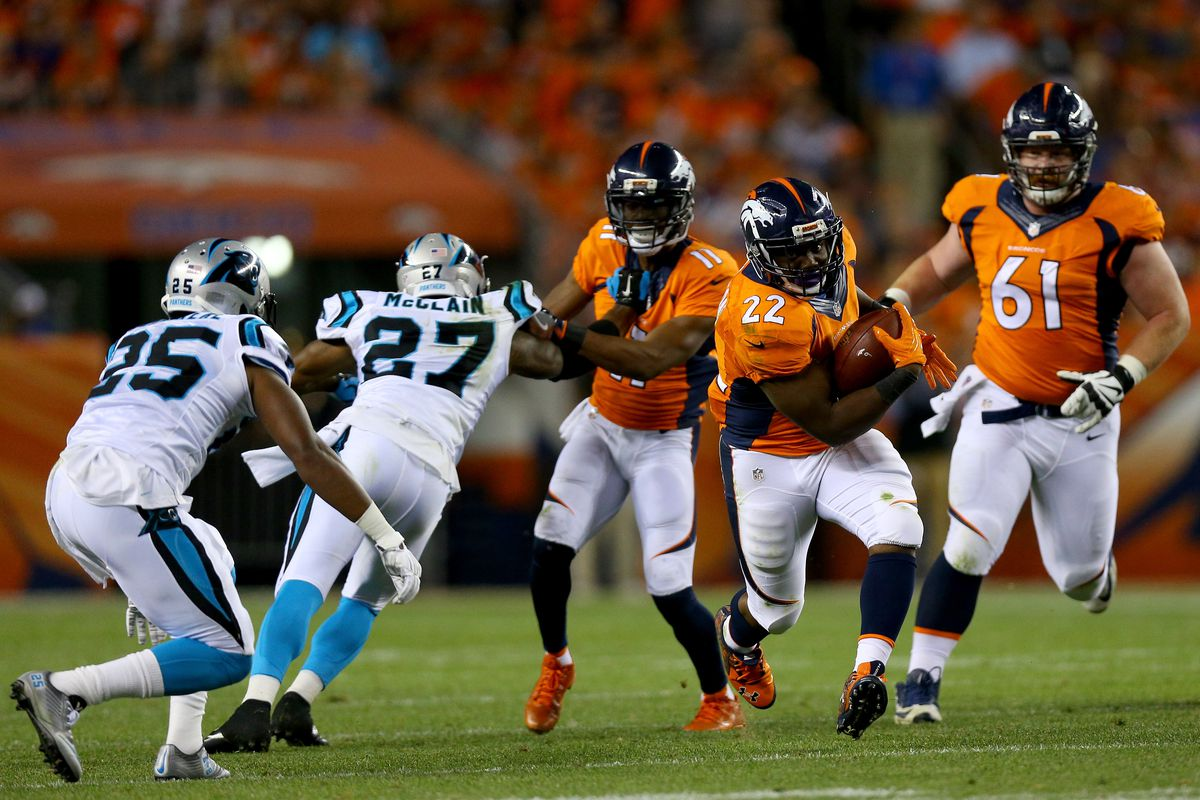 DENVER, CO -  Running back C.J. Anderson #22 of the Denver  Broncos runs the ball in the second half against the Carolina Panthers defense at Sports Authority Field at Mile High Stadium.