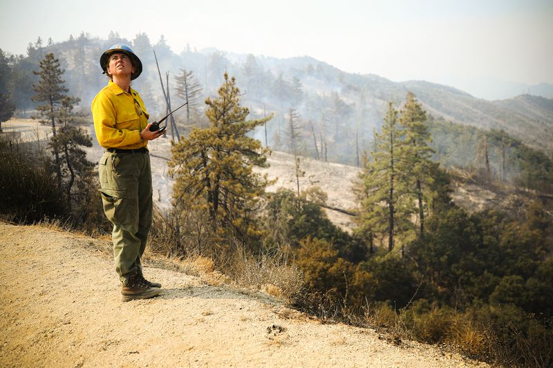 An employee of the US Forest Service monitors a firefighting helicopter making water drops