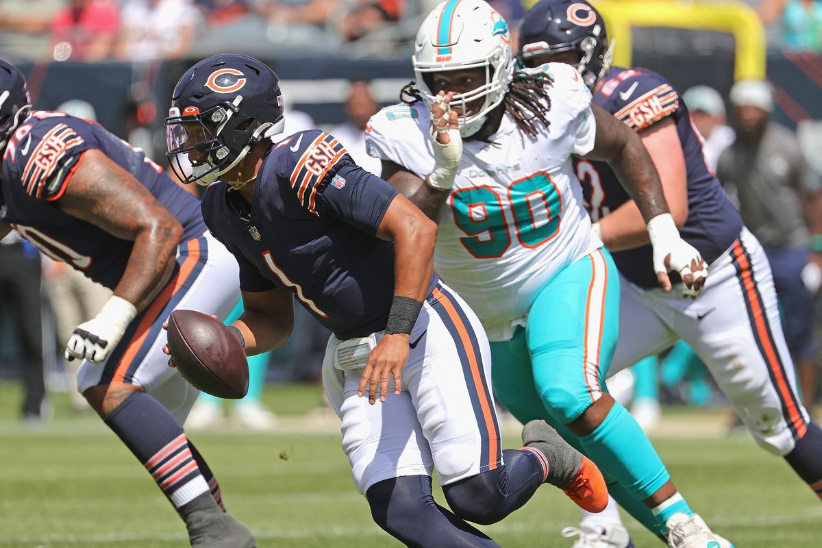Quarterback Justin Fields is chased from the pocket in the Bears' 20-13 victory over the Dolphins in a preseason game Saturday.