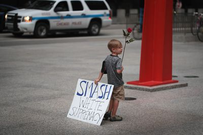 """A young boy holds a sign that reads, """"Smash white supremacy."""""""
