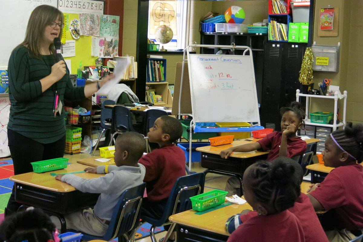 Cornerstone Preparatory Academy teacher Katelyn Woodard uses an amplifier with a wireless microphone to project her voice in the classroom during a lesson on measurement with her second grade students on Jan. 13, 2015.  Woodard purchased the amplifier last November when she started losing her voice.