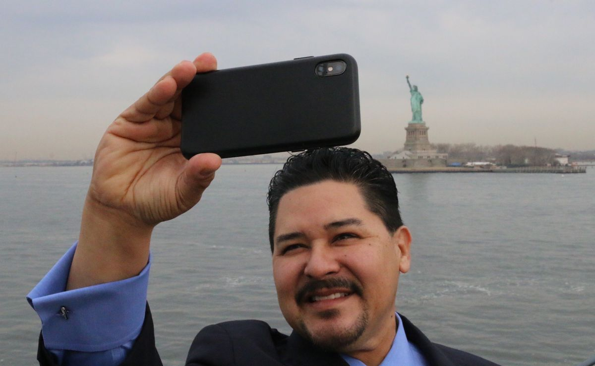 Schools Chancellor Richard Carranza poses for a selfie with the Statue of Liberty on the Staten Island Ferry.