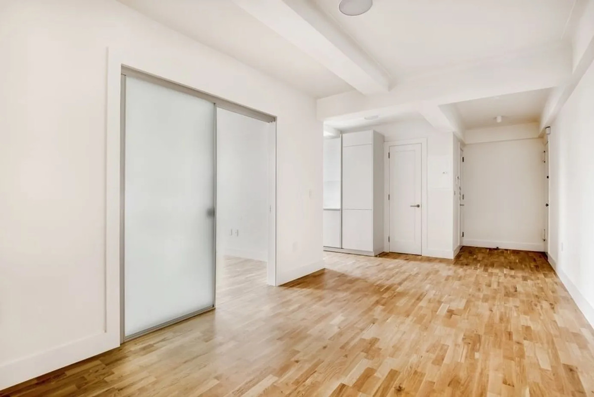 A living area with hardwood floors, a sliding door that leads to a bedroom, and beige walls.