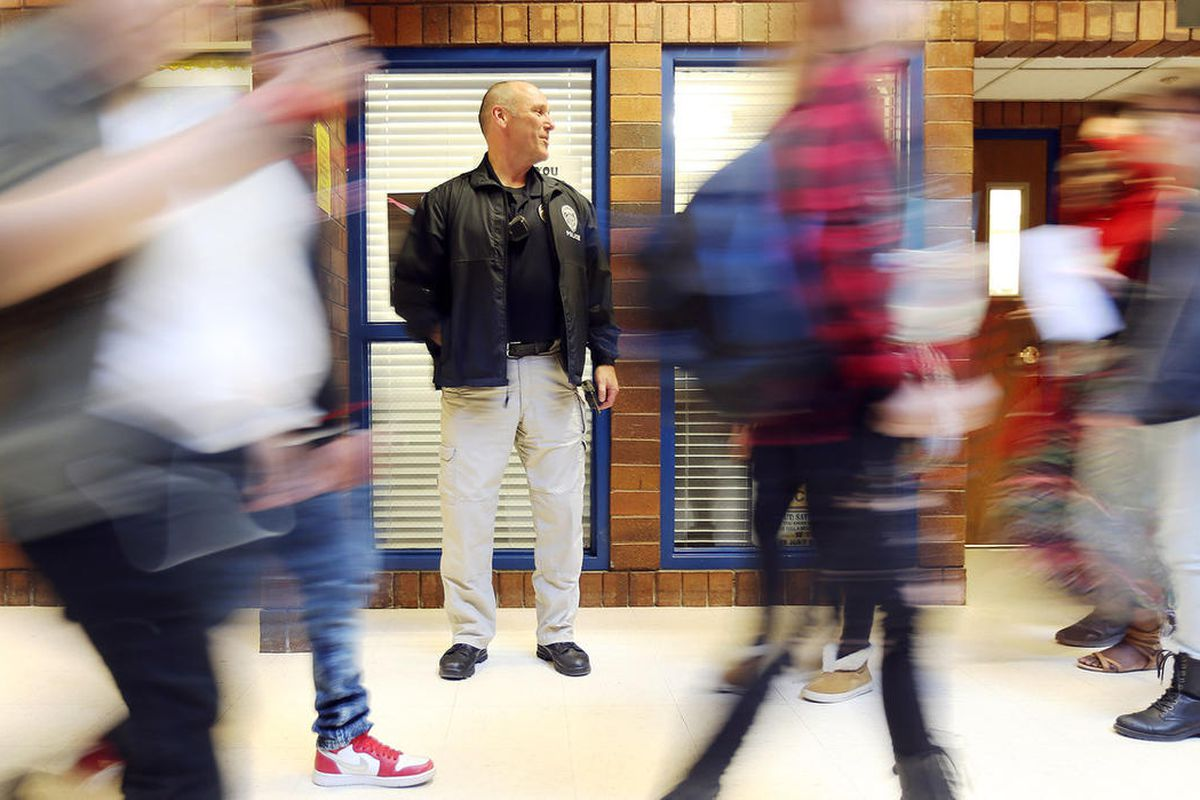 FILE - Unified police detective Jerry Byam stands in a hallway as school ends for the day at Taylorsville High on Monday, March 13, 2017. According to Utah school and police officials, sexting is so widespread that many teens just accept it as commonplace