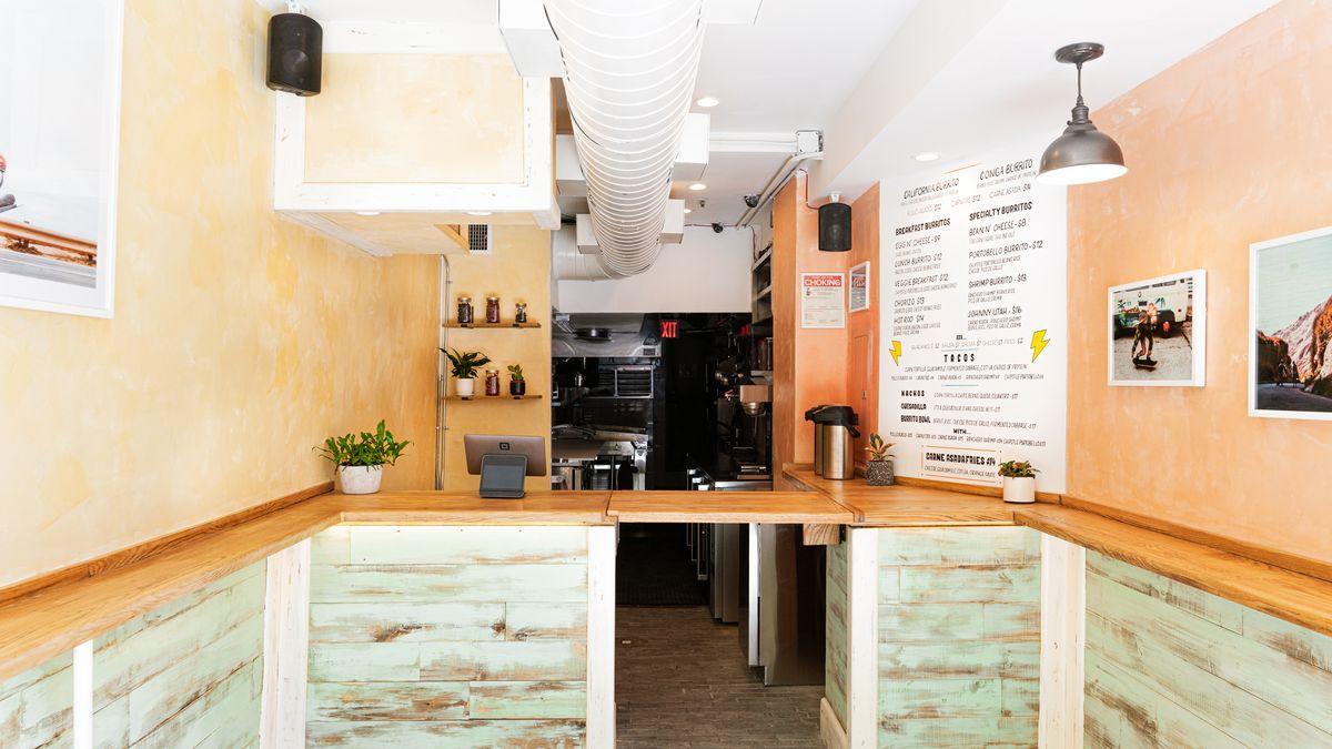 A brightly lit storefront, whose menu advertises tacos, burritos, and carne asada fries