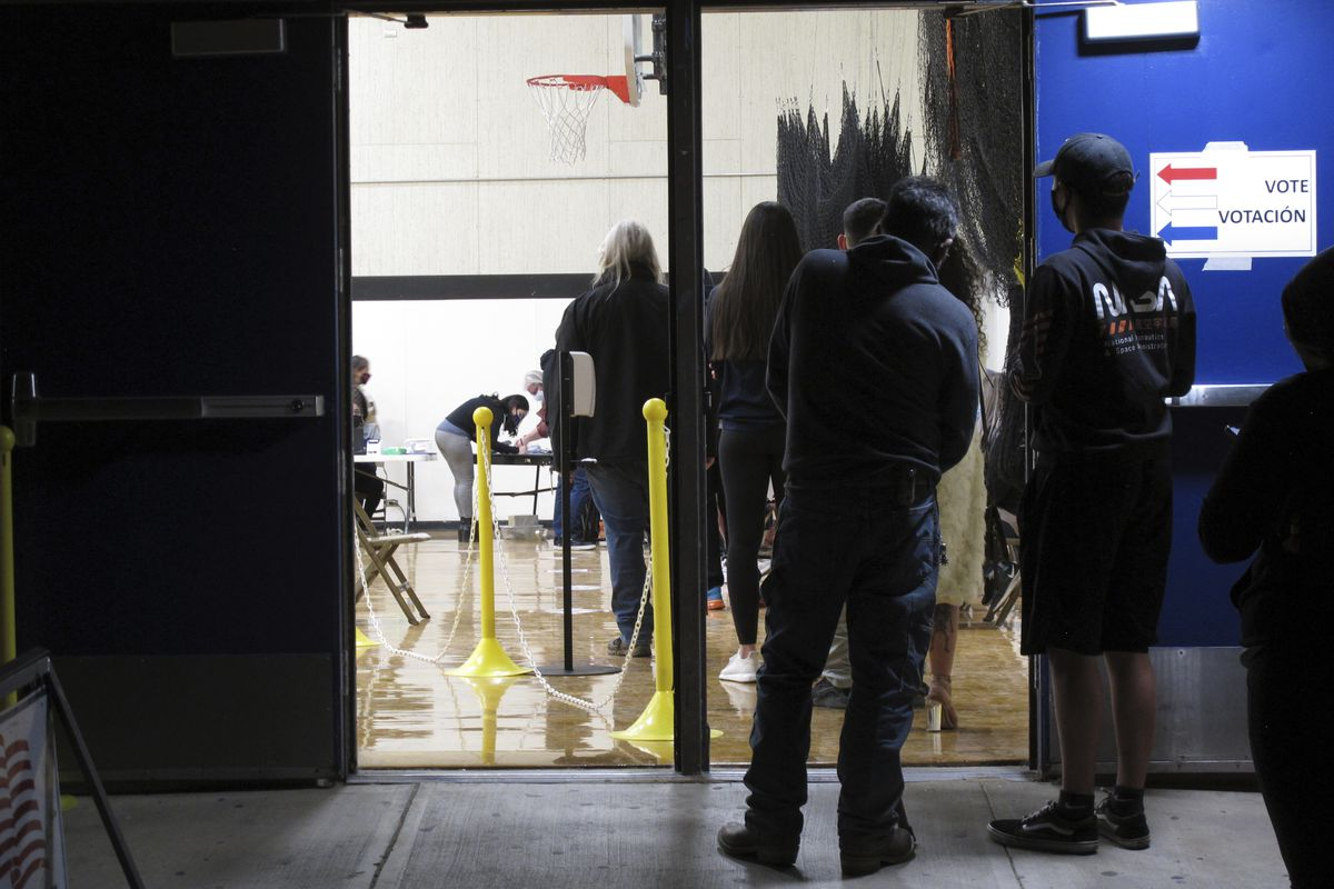 In this Nov. 3, 2020, file photo, some of the last voters wait in line to cast their ballots after the line was cut off at 7 p.m., local time, outside the gymnasium at Reed High School in Sparks, Nev. Everyone in line when the polls closed at 7 p.m. was allowed to vote in Washoe County, where registration is split evenly between the two major parties in the northern part of the state.
