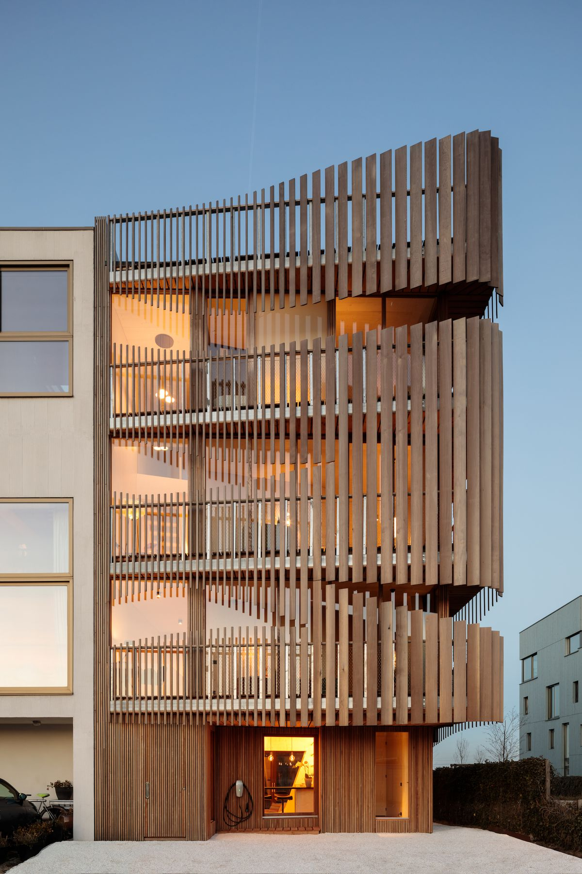 Four-story building with wooden louvers.