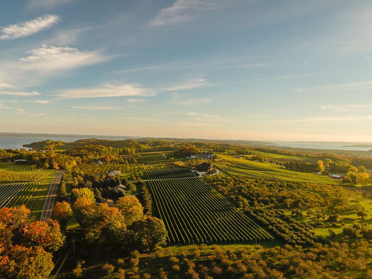 An aerial view of Old Mission Peninsula in Michigan. There are fields and trees with colorful autumn leaves.