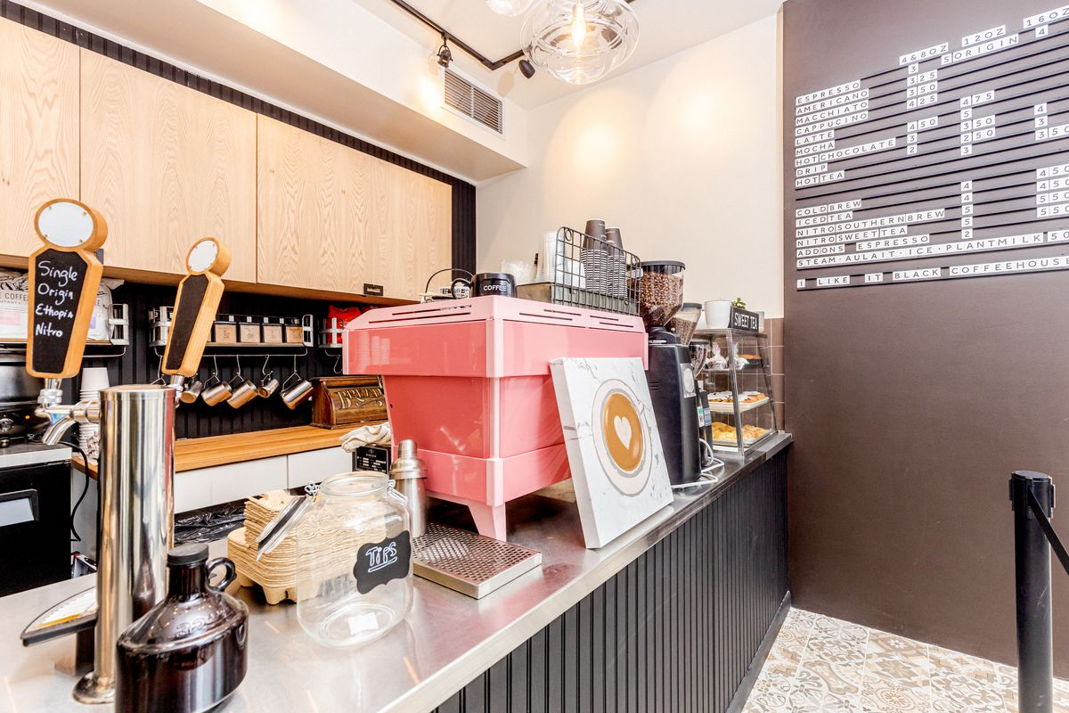 The interior of a small coffee shop, with levers for coffee on-tap and a menu of hot and cold beverages in the background