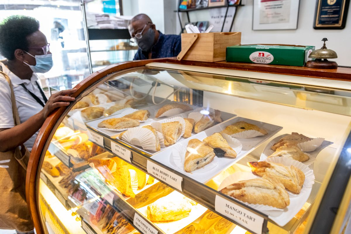 A woman looks into a glass case full of pastries.