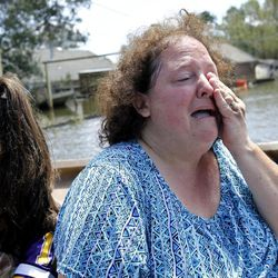 Angela Serpas cries as she sees her flooded home for the first time since Hurricane Isaac pushed a 10-foot storm surge into Braithwaite, La., Saturday, Sept. 1, 2012. At right is her daughter Lainy Serpas, 11.  While New Orleans streets were bustling again and workers were returning to offshore oil rigs, thousands of evacuees couldn't return home to flooded low-lying areas of Louisiana and more than 400,000 sweltering electricity customers in the state remained without power.