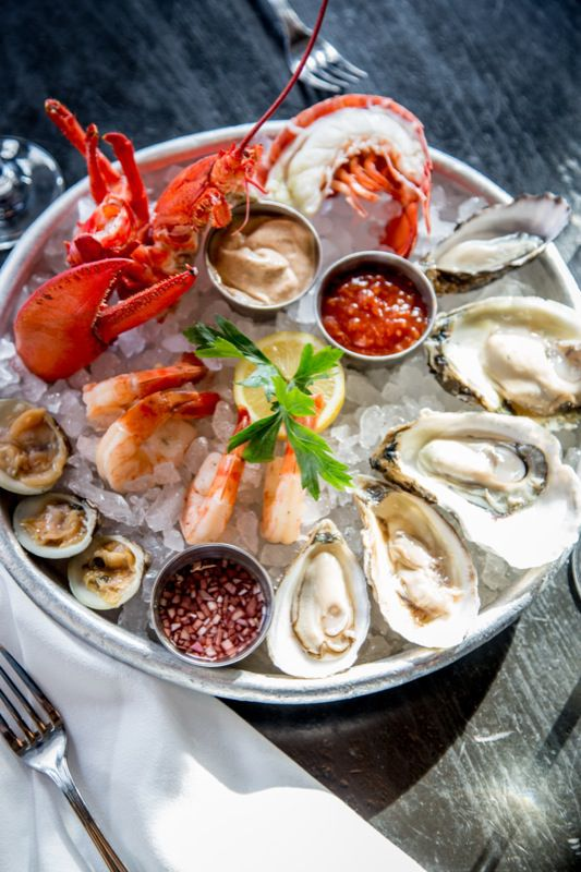 A fork sits on a napkin next to a large round plate of oysters