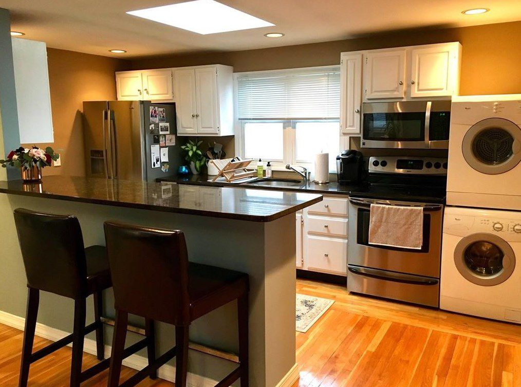 A kitchen with a counter with stools in front of it, and there's a washer-dryer stacked next to the oven.