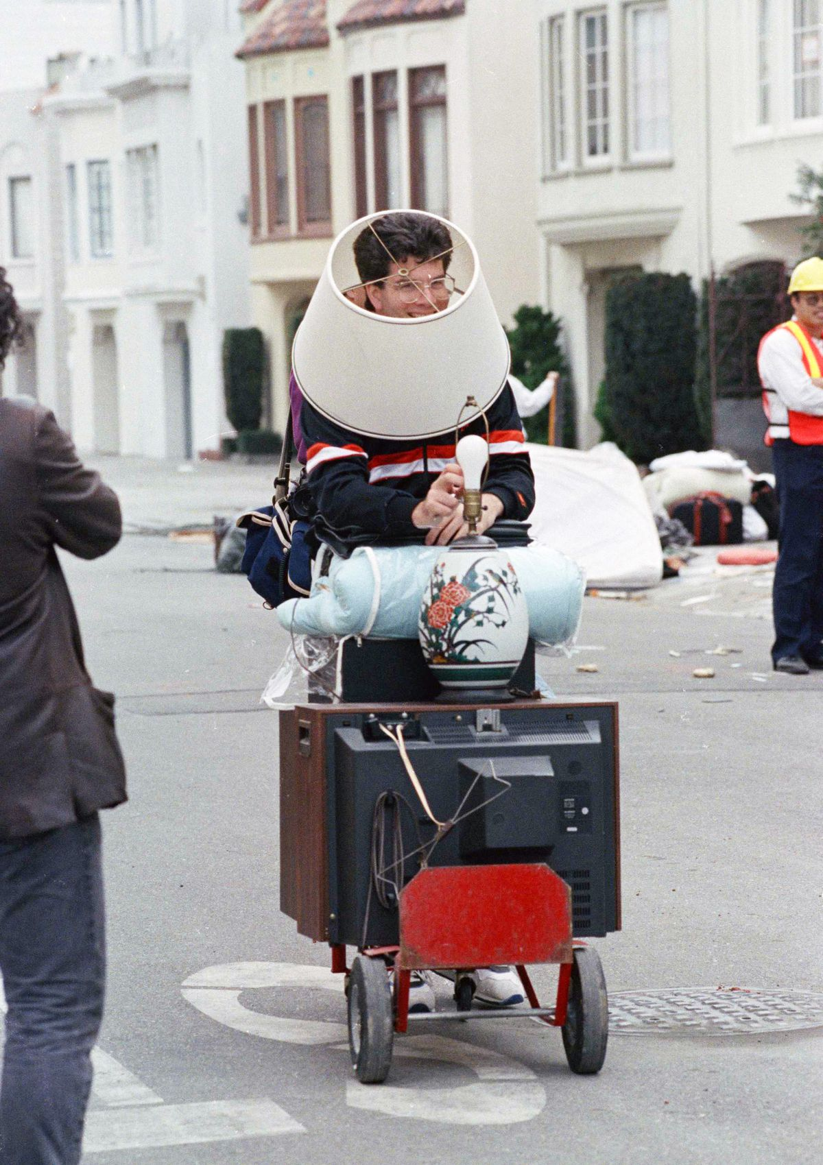 A man with a lampshade on his head as he pushed around a TV, lamp, and other belongings on a city street.
