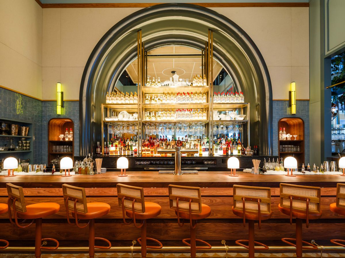 A long bar with a curved mirror behind it.