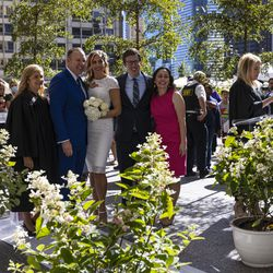 A newlywed couple takes photos with family outside the Wrigley Building on N Michigan Ave during the Meet Me on The Mile Sunday Spectacle Sunday, Sept. 26, 2021. 50 couples were married outside the Wrigley Building during The Mile Sunday Spectacle. | Anthony Vazquez/Sun-Times
