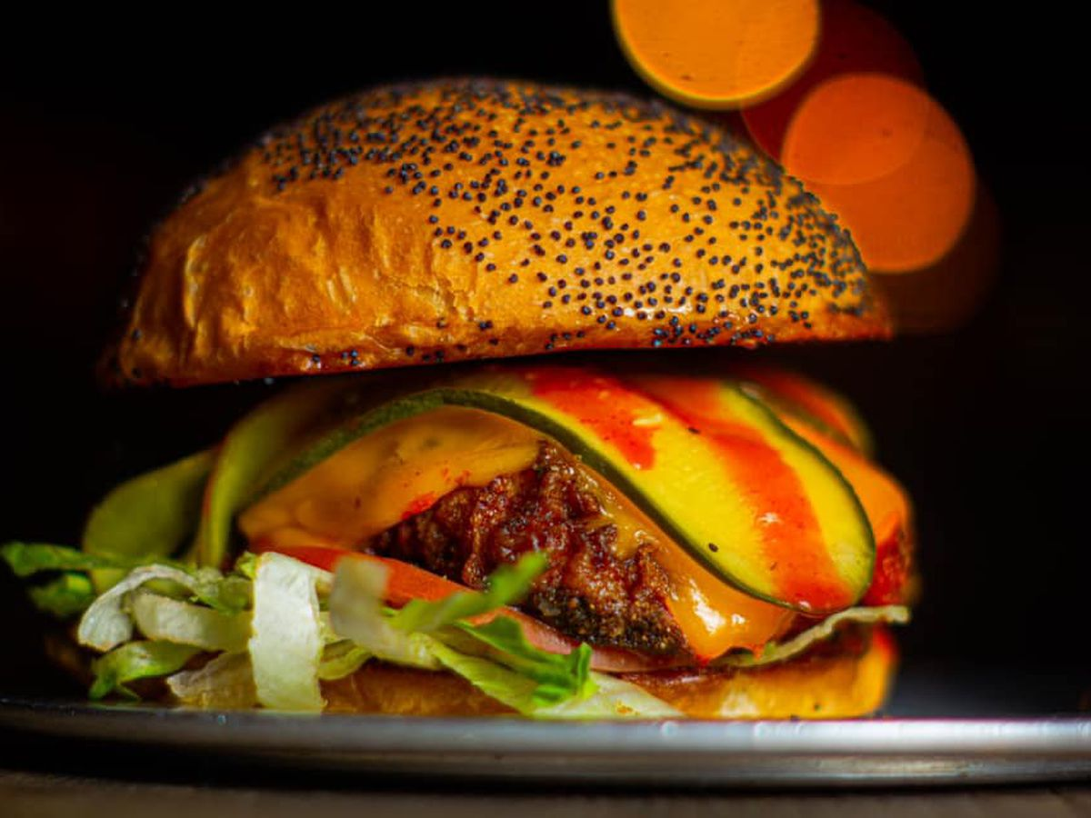A spicy chicken sandwich garnished with pickles, hot sauce, cheese, and lettuce, served on a poppy seed bun.