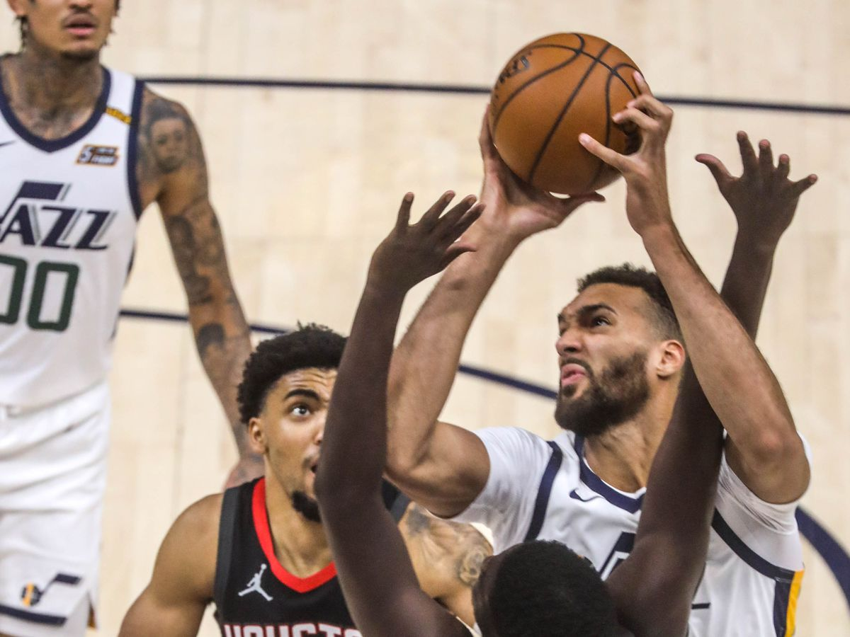 Utah Jazz center Rudy Gobert (27) moves with the ball against Houston Rockets Khyri Thomas (20) as the Utah Jazz and the Houston Rockets play an NBA basketball game at Vivint Arena in Salt Lake City on Saturday, May 8, 2021.