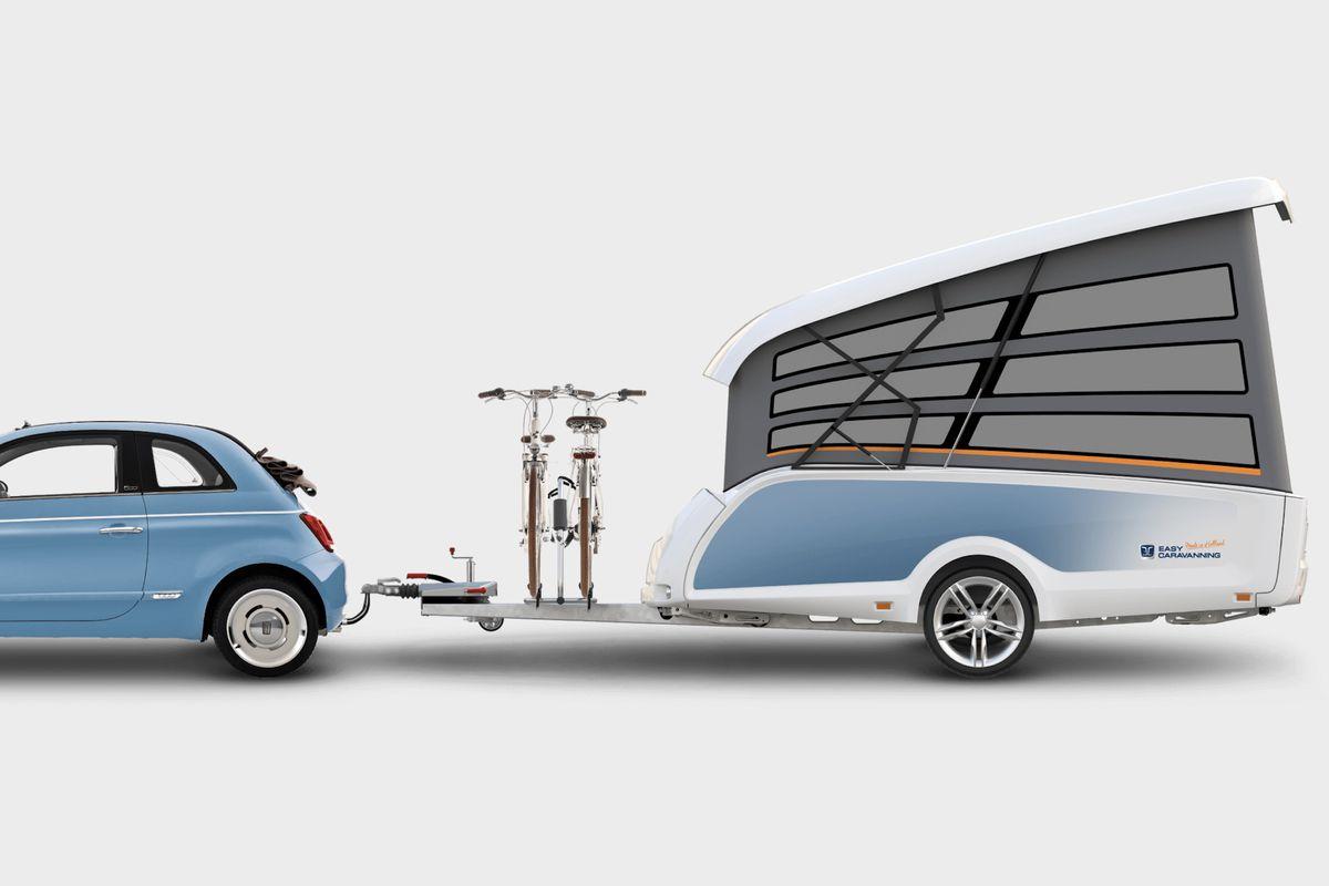 A small light blue car pulls a light blue pop-up trailer with bikes on racks.