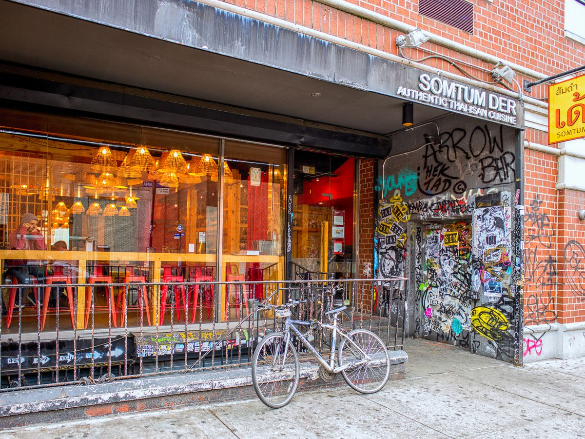 A restaurant storefront with a yellow table and a bike in front.