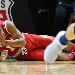 Utah Utes guard Brandon Taylor (11) holds his face after being hit by Brigham Young Cougars guard Nick Emery (4) as Utah and BYU play in the Huntsman Center in Salt Lake City Wednesday, Dec. 2, 2015. Utah won 83-75.