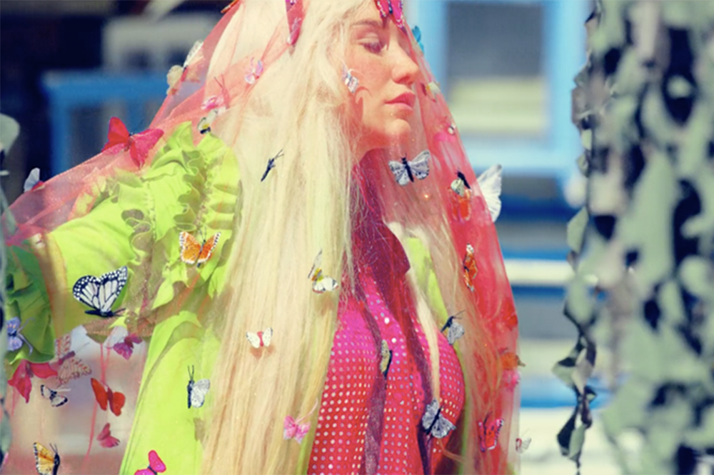 """Kesha wears a Gucci coat and a Gasoline Glamour butterfly veil in her """"Praying"""" music video."""